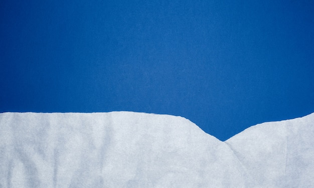 Blauwe achtergrond met witte verfrommelde gescheurde document elementen