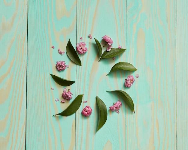 Blauwe achtergrond versierd frame met blad en bloemen geïsoleerd plat leggen