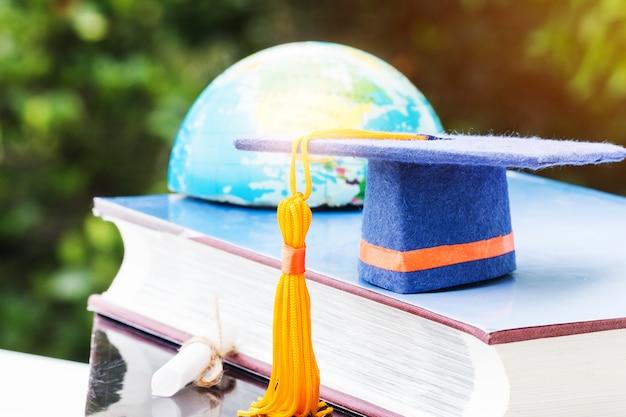 Blauwe afstuderen cap op leerboek met vervaging van amerika earth world globe