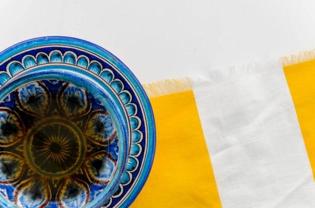 Blauwe aftrekselkop en schotel op tafelkleed tegen witte achtergrond