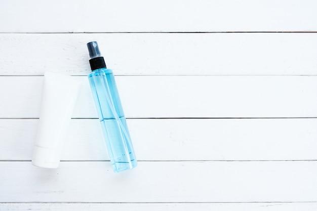 Blauwe alcohol en gelalcohol voor handreiniging, geplaatst op een witte houten vloer met groene bladeren.