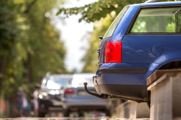 Blauwe auto geparkeerd op zonnige straat, rode stoplichten, haak voor het slepen van de trailer
