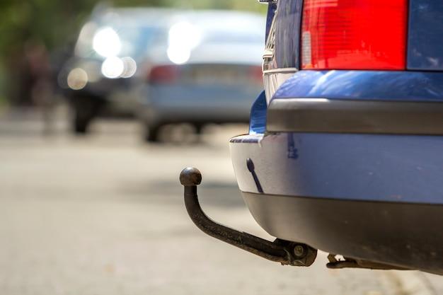 Blauwe auto geparkeerd op zonnige straat, rode stoplichten, haak voor het slepen van trailer, trekhaak of trekhaak.