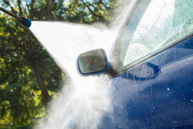 Blauwe auto in een autowasserette