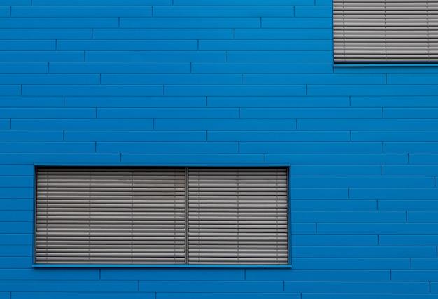Blauwe bakstenen muur met grijze vensterblinds