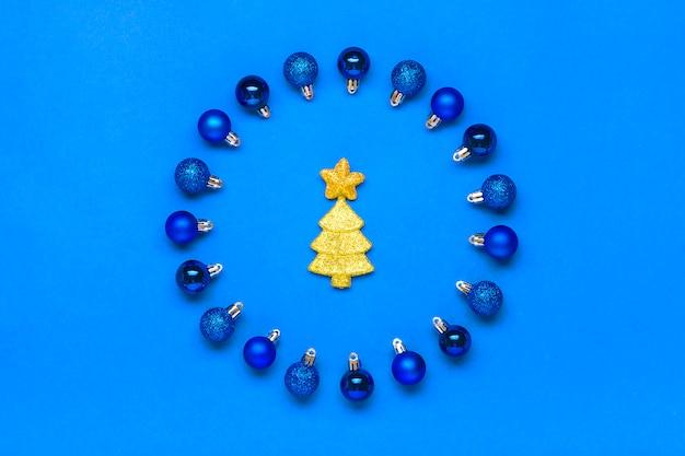 Blauwe bal in de vorm van een ronde, een boom en een ster versierd met gouden lovertje op een klassieke blauwe achtergrond kleur van het jaar 2020 vrolijk kerstfeest, gelukkig nieuwjaar creatief concept plat leggen