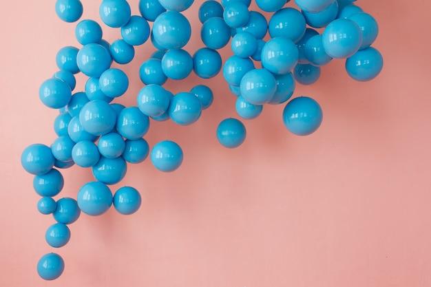 Blauwe ballonnen, blauwe bubbels op roze achtergrond. moderne, punchy pastelkleuren