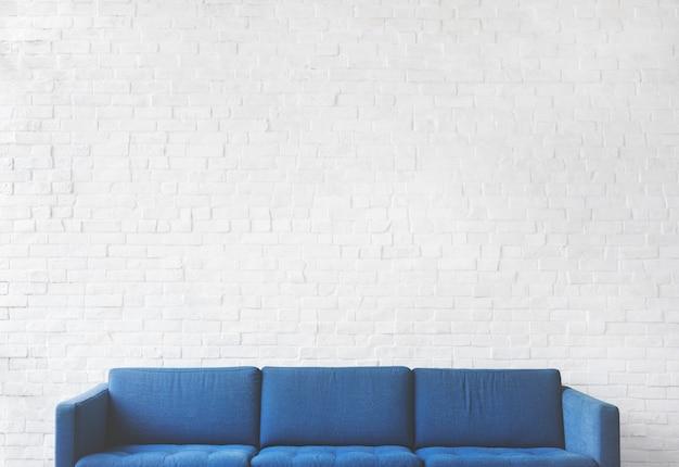 Blauwe bank met witte bakstenen muurachtergrond