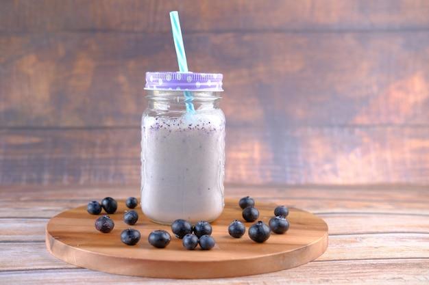 Blauwe bessen milkshake in een glas op tafel