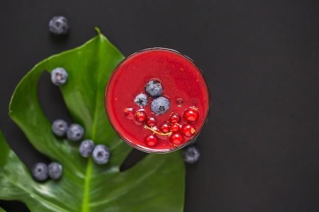 Blauwe bessen op smoothie en groen blad tegen zwarte achtergrond