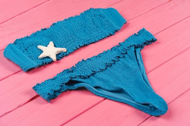 Blauwe bikini op felroze hout