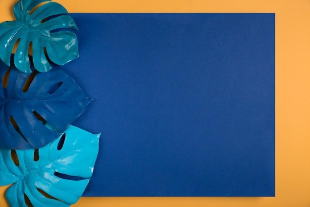 Blauwe bladeren op donkerblauwe rechthoek met kopie ruimte