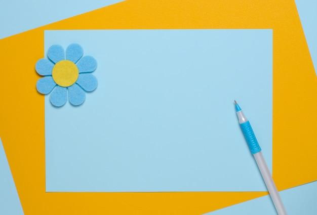 Blauwe bloem gemaakt van vilt op een blauwe en oranje achtergrond.