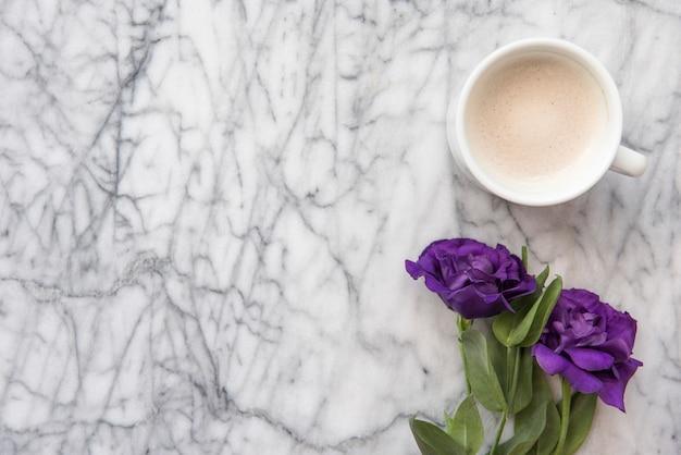 Blauwe bloemen met koffiekop op tafel
