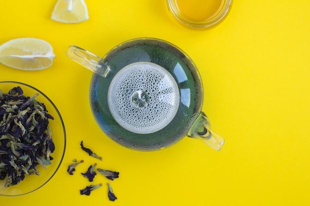 Blauwe bloementhee in de glastheepot op de gele achtergrond