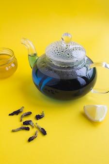 Blauwe bloemthee in de glastheepot op geel