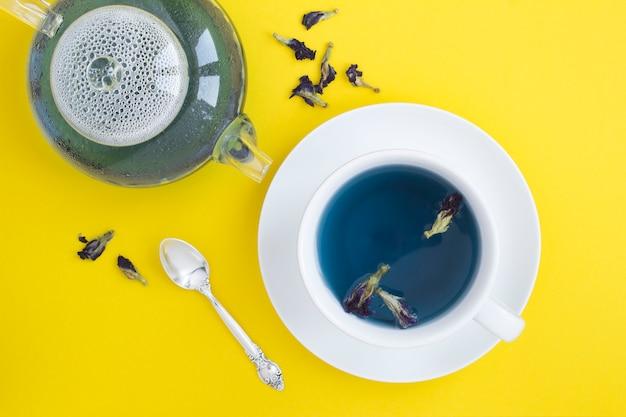 Blauwe bloemthee in de witte kop en glastheepot op geel