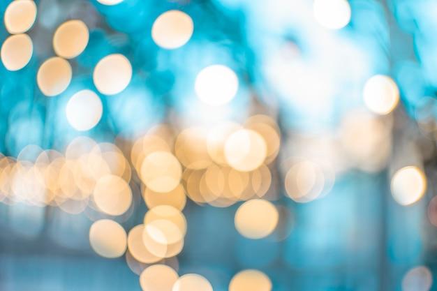 Blauwe bokeh. vakantie verlichting en decoratie concept - garland bokeh licht over blauwe achtergrond