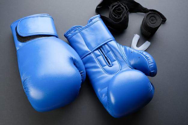 Blauwe bokshandschoenen en verbanden op een donkere achtergrond