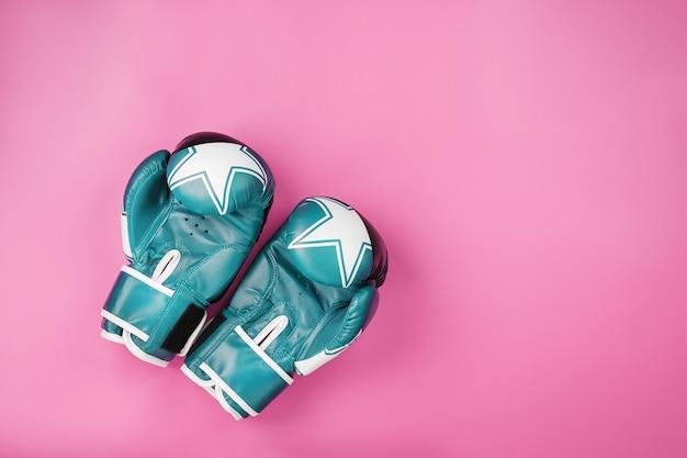 Blauwe bokshandschoenen op een roze achtergrond, vrije ruimte