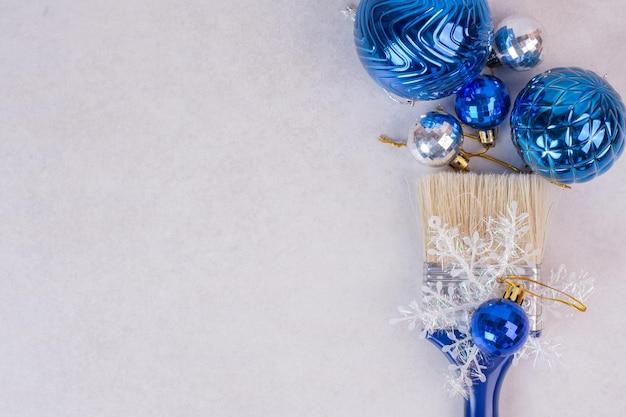Blauwe borstel met kerstballen op witte tafel.