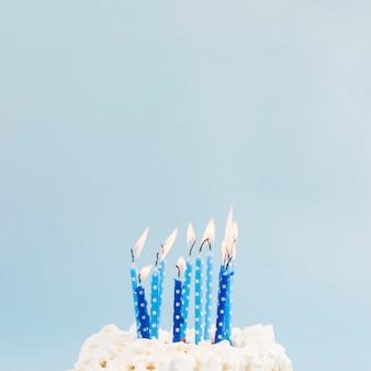 Blauwe brandende kaarsen over de verjaardagscake tegen blauwe achtergrond