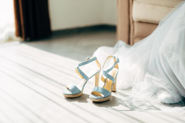 Blauwe bruidsschoenen met hoge hakken op de vloer bij de sleep van de trouwjurk
