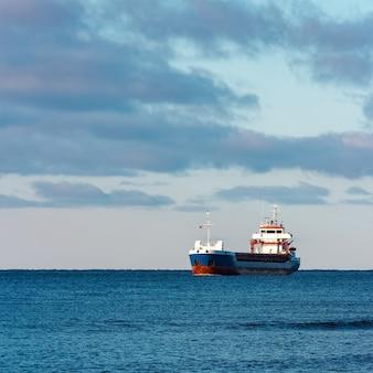 Blauwe bulkcarrier die in stilstaand water vaart