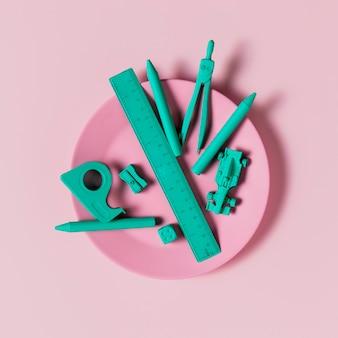 Blauwe bureautoebehoren op roze plaat