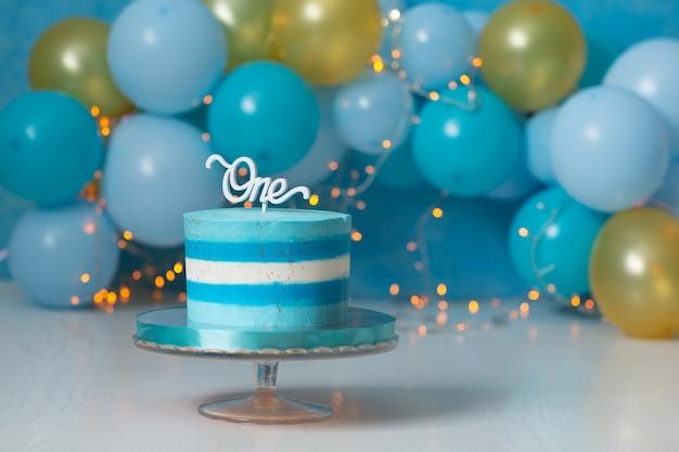 Blauwe cake gestreept op een stand en ballonnen