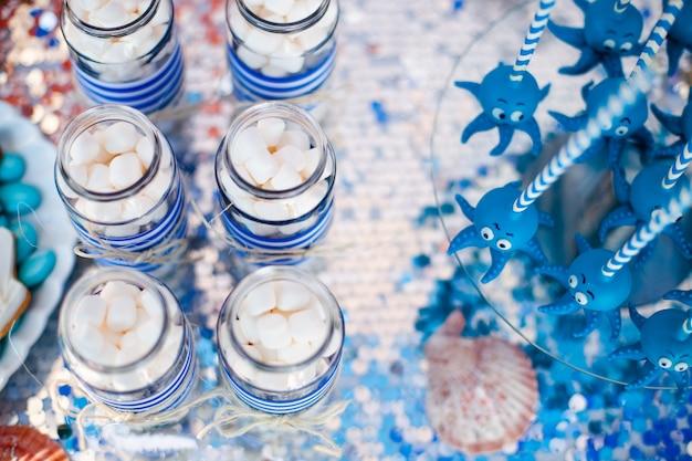 Blauwe cake knalt grappige octopussen gedeeld op de glazen ronde plaat en potten met marshmallow.