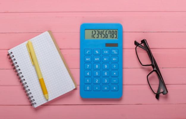 Blauwe calculator met notitieboekje en glazen op roze houten