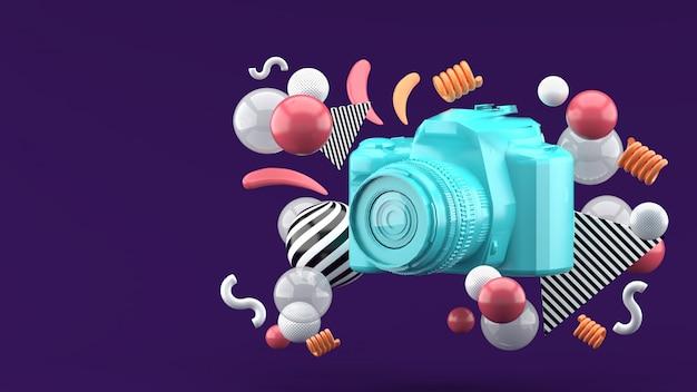 Blauwe camera omgeven door kleurrijke ballen op paars. 3d render.