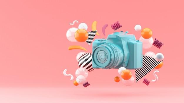 Blauwe camera omgeven door kleurrijke ballen op roze. 3d render.