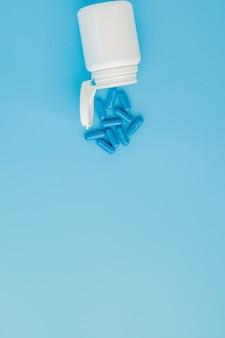 Blauwe capsules, pillen op een blauwe achtergrond. capsules in een witte pot. vitaminen, voedingssupplementen