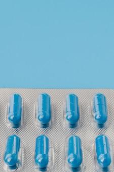 Blauwe capsules, pillen op een blauwe muur. vitaminen, voedingssupplementen voor de gezondheid van vrouwen