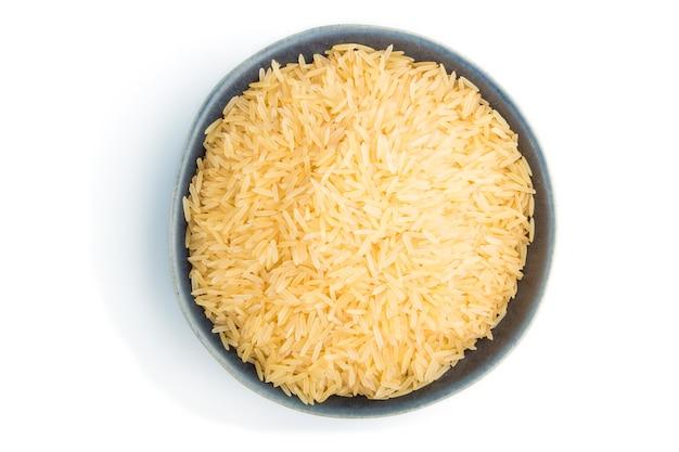 Blauwe ceramische kom met ruwe gouden rijst die op witte oppervlakte wordt geïsoleerd