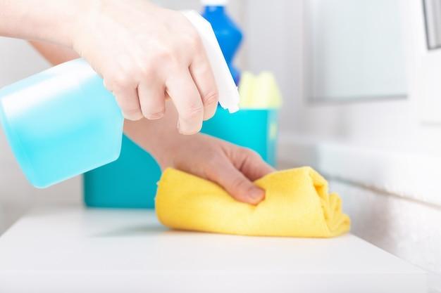 Blauwe chloor flessenspray. vrouw met behulp van wasmiddel en veeg. reinigen met reinigingsspray.
