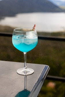 Blauwe cocktail bovenop zwarte tafel