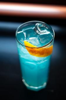 Blauwe cocktail in longdrink met ijs en sinaasappelschil