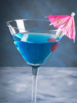 Blauwe cocktail in martini-glas met paraplu