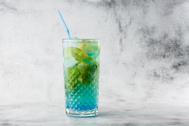 Blauwe cocktail met ijsblokjes en schijfjes citroen en limoen. blauwe lagune zomer coctail. ijsblauwe limonade. bovenaanzicht, kopieer ruimte. reclame voor café. barmenu. horizontale foto.