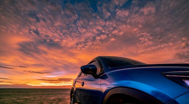 Blauwe compacte suv-auto met sport, modern en luxe design geparkeerd op betonweg aan zee bij zonsondergang. reis op vakantie op het strand.