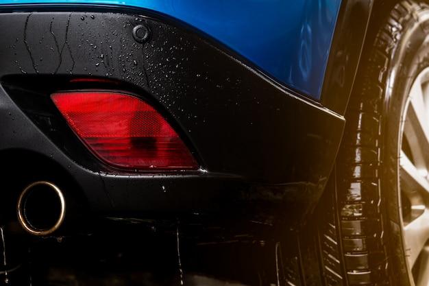 Blauwe compacte suv-auto met sportontwerp wast met water. auto zorg service bedrijfsconcept. auto bedekt met druppels water na reiniging met water en schuimspray. auto-industrie concept