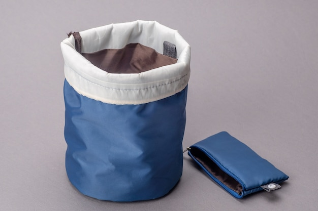 Blauwe cosmetische tas geïsoleerd op een grijze achtergrond