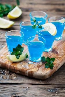 Blauwe curacao likeur met citroen op de houten tafel