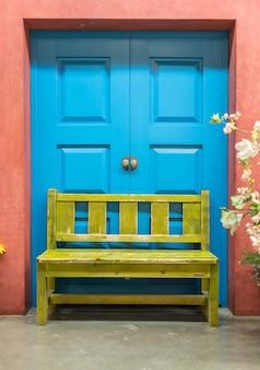 Blauwe deur en gele bankje