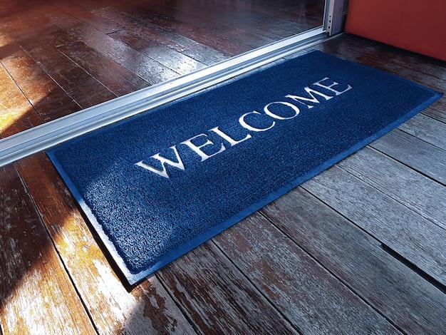 Blauwe deurmat met welkomsttekst voor winkel