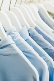 Blauwe dingen voor vrouwen hangen aan hangers in de winkel.