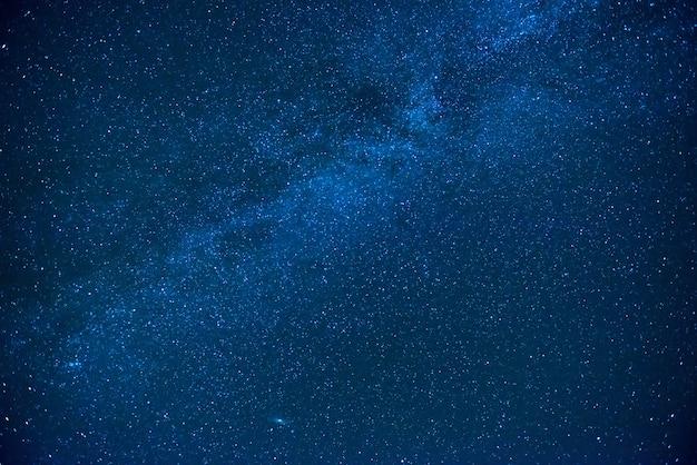 Blauwe donkere nachtelijke hemel met veel sterren. melkweg kosmos achtergrond